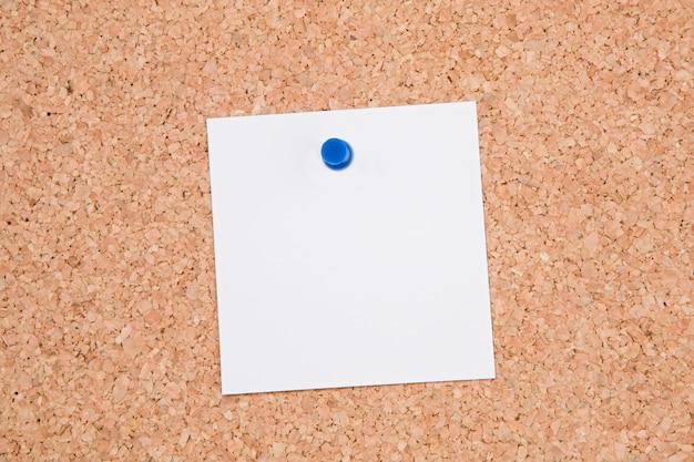 ブランクに1枚の紙が入ったコルクの掲示板