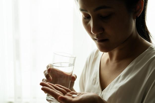 落ち込んでいる女性の手は、コップ1杯の水で薬を保持します