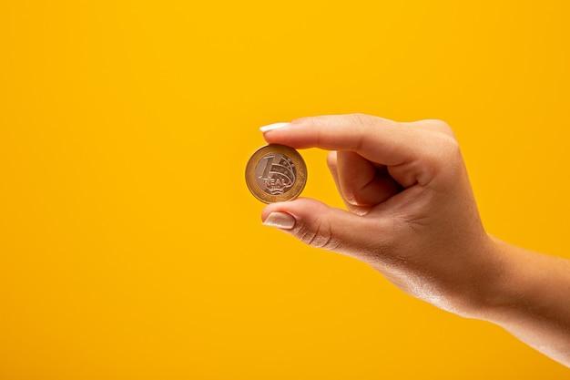 ブラジル金融概念の1つの本物のコインを持っている手。