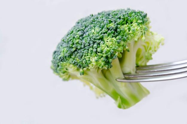 白で隔離されるフォークに熟した1つの新鮮なブロッコリーをクローズアップ。生ブロッコリーのサラダの一口