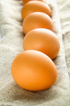 白い木製のテーブルの黄麻布の1行で茶色の生の鶏の卵。料理の食材。