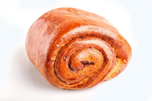 白い背景で隔離のシナモンと1つのパン