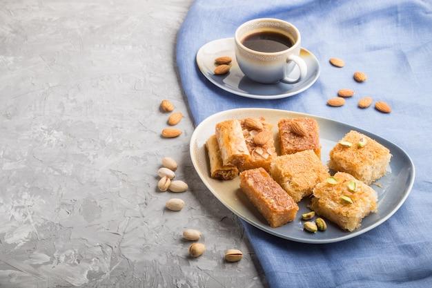 伝統的なアラビアのお菓子と灰色のコンクリートの表面にコーヒー1杯。側面図、コピースペース。