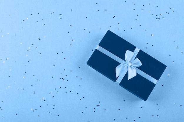 明るい青の背景に輝く1つの青いギフトボックス。クリスマス、誕生日、休日のコンセプトです。トップビュー、フラットレイアウト、コピースペース