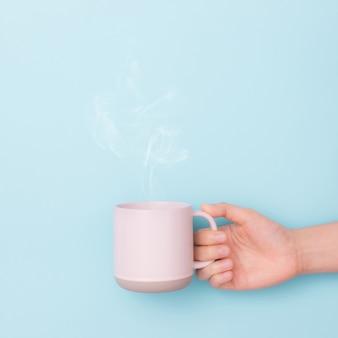 青色の背景に手の中にコーヒー1杯