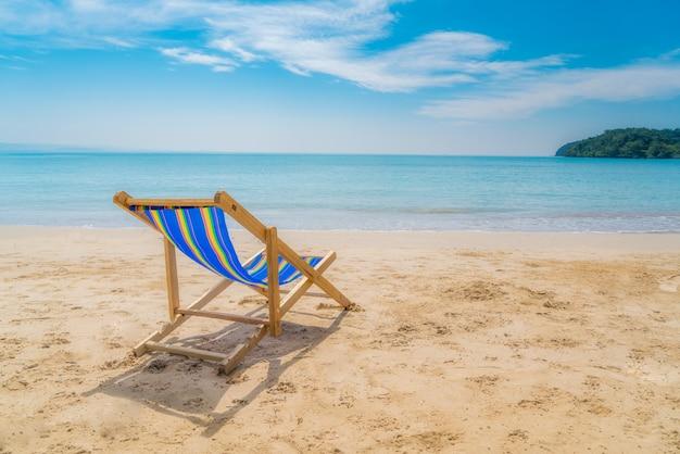 青い空と夏の海と白い砂の上に1つのビーチチェア