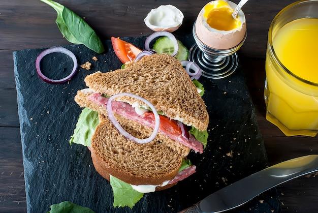サンドイッチ、卵、カップコーヒー、ジュース1杯の朝食