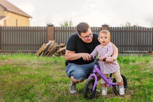 若い父親は、かわいい小さな1歳の幼児の女の子子供とバランスバイクと過ごす
