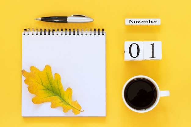 Деревянный календарь 1 ноября чашка кофе, блокнот с ручкой и желтый лист на желтом фоне