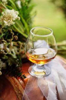 ブランデーグラス、花の横のテーブルに1杯のグラス