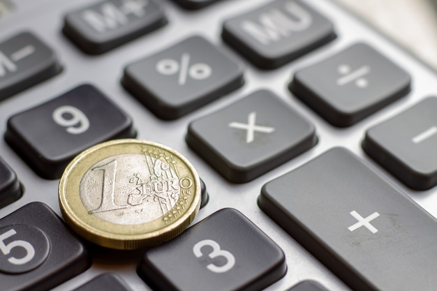 1ユーロ硬貨とキーボード電卓のクローズアップ。経済金融ローン担保抵当貸付金利の事業コンセプト。