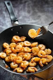 おいしい食欲をそそるジューシーな皮をむいたエビのフライパンをクローズアップし、1本のエビをフォークに乗せます。