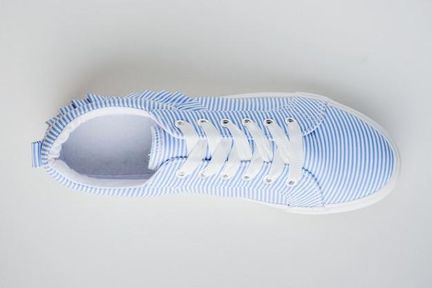 白い上面に1つの青のストライプの女性スニーカー。フラットレイミニマル