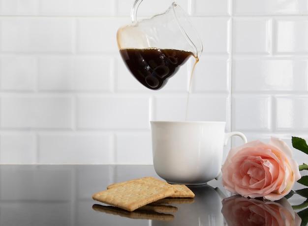 ビスケットと1つの桃色のバラと白いセラミックカップ