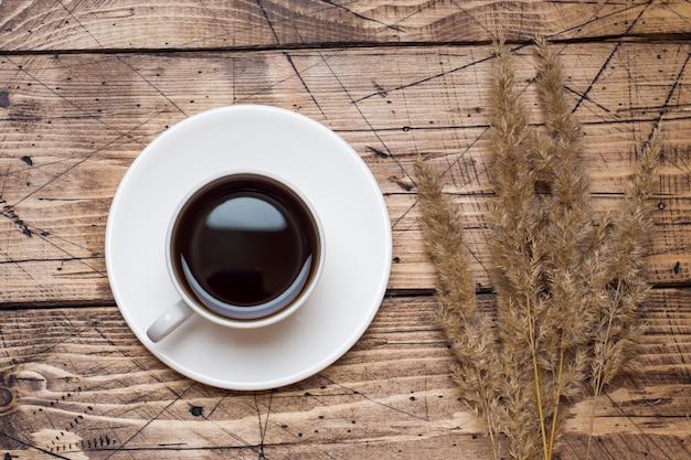 秋の花と木製の背景にコーヒー1杯