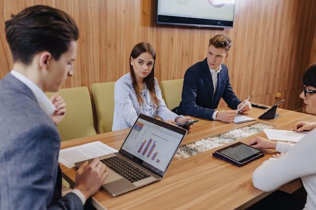 オフィスワーカーはノートパソコンのために1つの机で会議を開きます