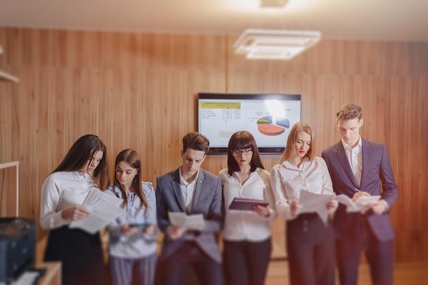 人々の大規模なチームは、木製の壁に大きなテレビを背景に、ラップトップ、タブレット、紙のための1つのテーブルで働いています。
