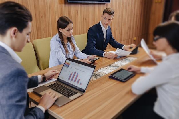 オフィスワーカーは、ノートパソコン、タブレット、紙の1つのデスクで会議を開催し、背景には木製の壁に大型テレビを設置