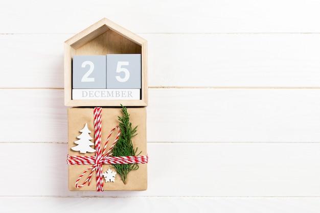 Рождественский календарь 1 декабря, рождественский подарок, еловые ветки на деревянном белом, вид сверху