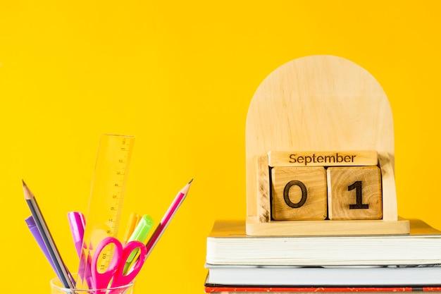 1 сентября на деревянном календаре среди учебников и ручек для занятий на желтом фоне