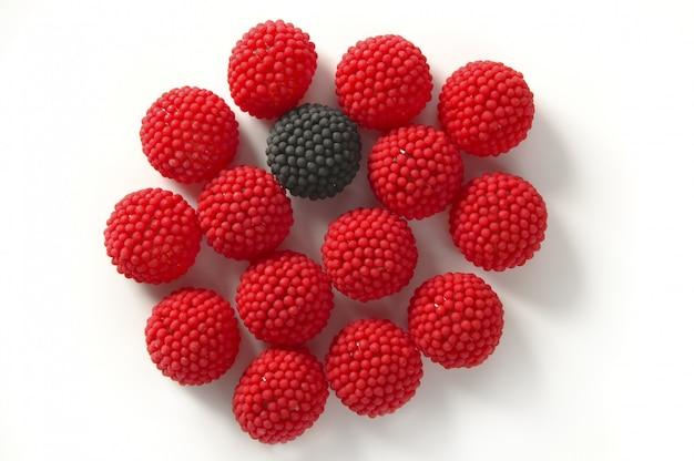 赤い果実の間に分離された1つの黒いキャンディーベリー