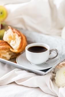 焼きたてのクロワッサン、コーヒー1杯、ラナンキュラスの花の朝食