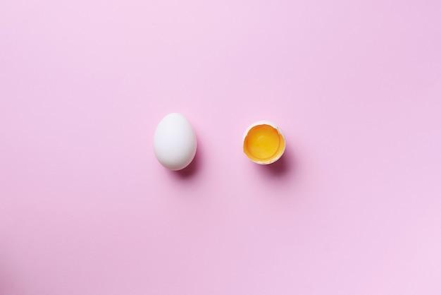 割れた卵とピンク色の背景上の全体1つの食品のコンセプト