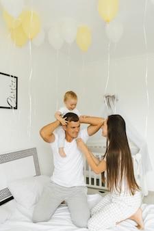 父、母とその幼い息子は朝のうちの1つで楽しんでいます