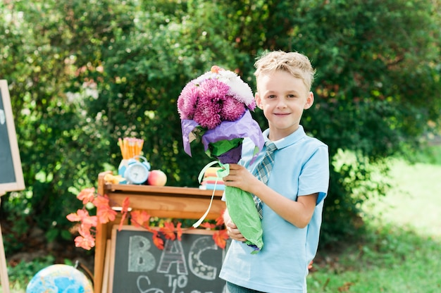 背景秋の公園の制服で花束を持つ美しい若い1年生の肖像画。