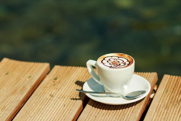 コーヒー、カプチーノ、ラテアート、ラテ。プロのコーヒー1杯が分離されました。温かい飲み物の素晴らしいカップ。