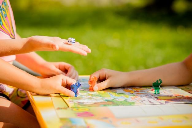 家族がボードゲームをプレイし、1人の子供が移動し、別のプレイヤーの駒を捕まえています。幼稚園のゲーム。ボードゲームと子供のレジャーコンセプト。赤い人の図を手に持った子供