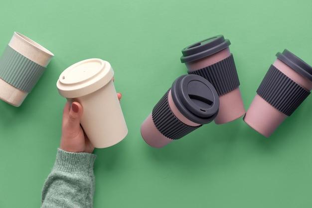 各種の竹製の旅行用の再利用可能なコーヒーまたはティーカップまたはシリコン断熱材入りマグ。女性の手に1杯。持続可能なライフスタイルのための環境に優しい廃棄物ゼロのアイデア