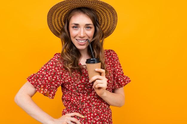 黄色の表面にコーヒー1杯の帽子をかぶった女性が分娩中に唇を抱えている