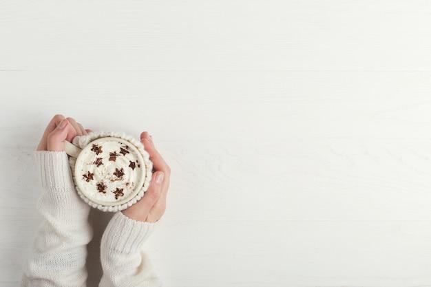 女の子はホイップクリームと一緒に、熱い冬の飲み物を1杯持っています。