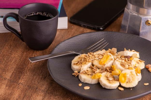 スライスしたバナナ、グラノーラ、砂糖漬けの果物と蜂蜜、トースト、コーヒー1杯のプレート