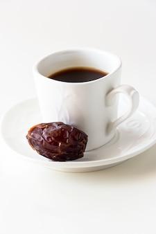 白い一杯のコーヒーと白い背景に分離された1つの日付。