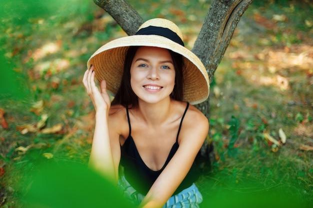帽子をかぶった美しく幸せな女の子が木の下に座っており、もう1人は勝利のクローズアップの肖像画としてサインを見せています。