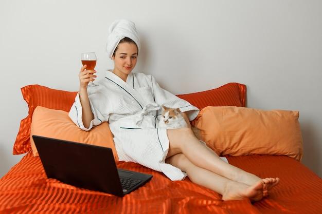 オンライン会議でバスローブと彼女の頭にタオルを着た女の子がワイングラスを1杯持っているラップトップで猫と一緒にベッドに座っています。
