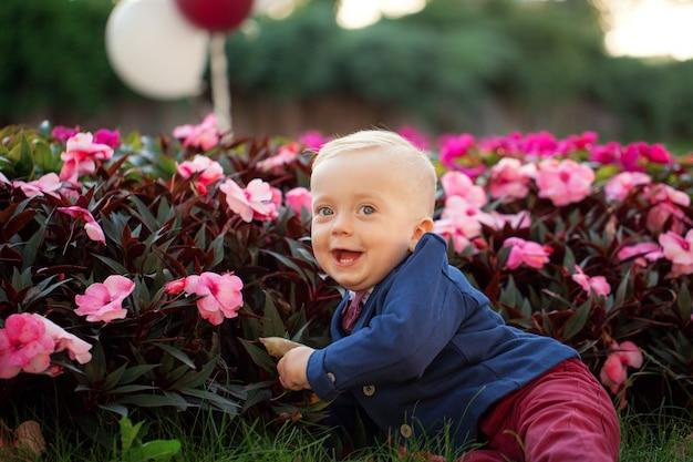 かわいい遊び心のある笑顔の金髪。風船で遊ぶ緑の芝生の上に座っている1歳の男の子。
