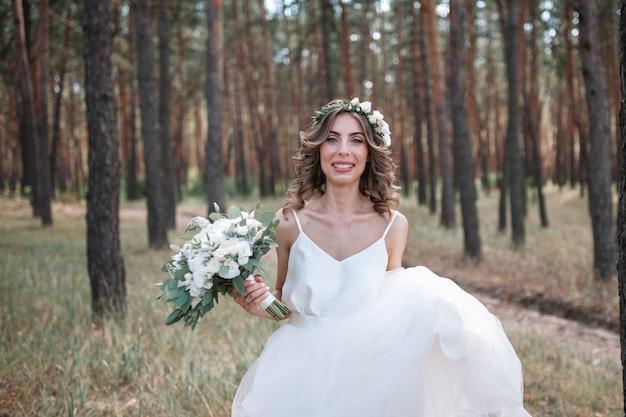 長い白いウェディングドレスの1つの美しい官能的な若いブロンドの花嫁の完全な長さの側面図