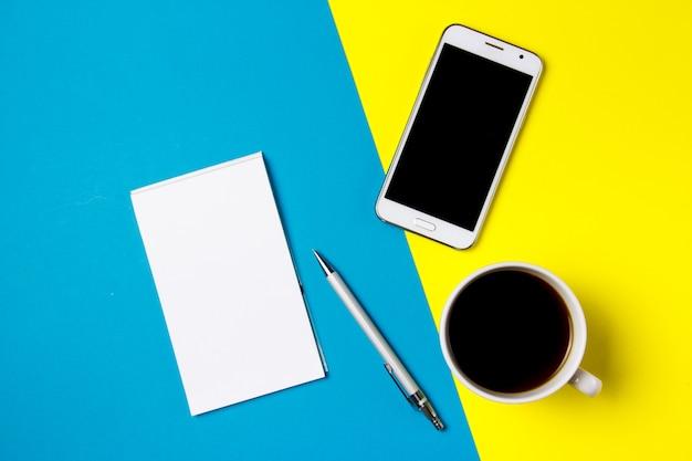 スマートフォン、メモ帳、黄色と青の芸術の背景にコーヒー1杯
