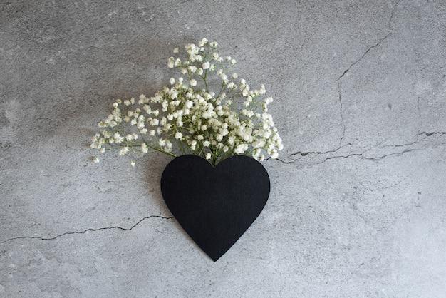花と葉で作られたハートマーク。最後の1つの花を持っている男性の手。