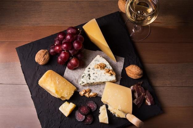盛り合わせチーズ、ナッツ、ブドウ、フルーツ、スモーク肉、ワイン1杯。ダークでムーディーなスタイル。テキスト用の空き容量。