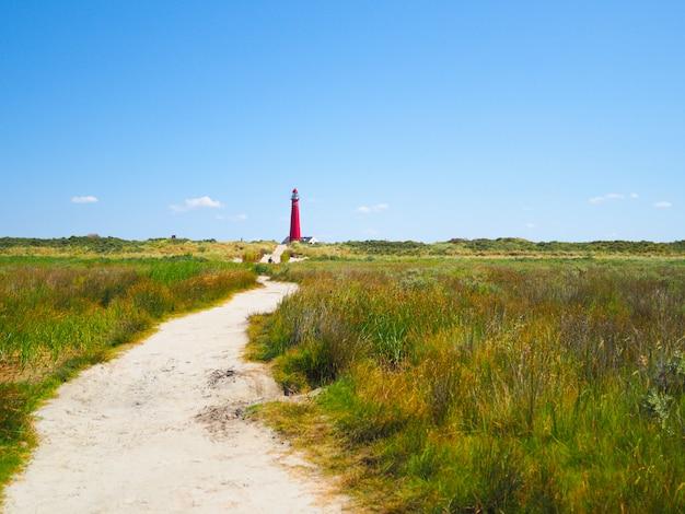 ノースタワー-シエルモニコーフ島の灯台、フリジア諸島の1つ、青い空を背景に砂丘の上の灯台