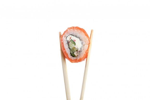 日本料理。白で隔離される木製の箸で寿司ロールの1つの平和