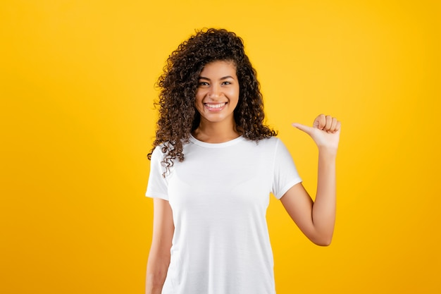 黄色で分離された1本の指を示す幸せな黒の女の子
