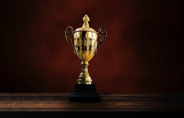 第一チャンピオン賞、最優秀賞と勝者のコンセプト、チャンピオンシップカップまたは黒とダークブラウンの壁の背景に木製のテーブルの勝者トロフィー