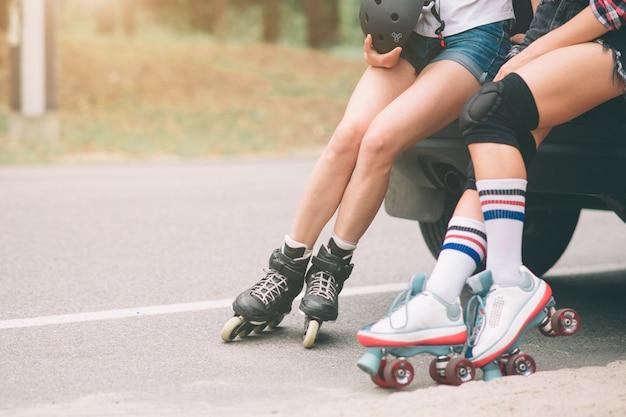 2人のスリムでセクシーな若い女性とローラースケート。 1人の女性にはインラインスケートがあり、もう1人の女性にはクワッドスケートがあります。女の子は太陽の光に乗る。