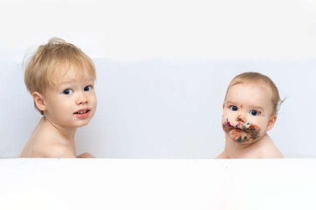 2人の子供がバスルームに座っており、1人の赤ちゃんは清潔で、もう1人の赤ちゃんは汚れています
