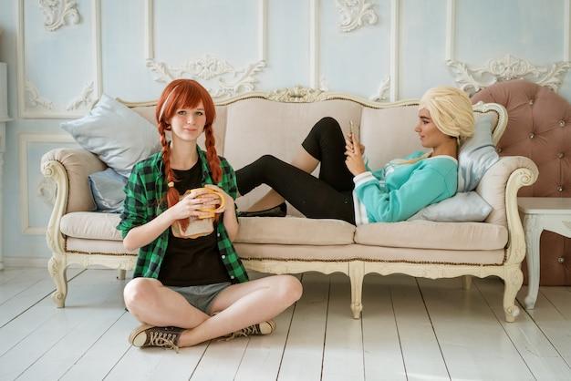 2人の友人、1人はソファに横になり、もう1人は床に座っています